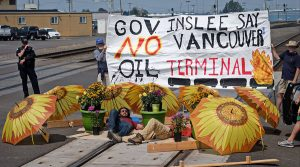 "Two adults lying down on train tracks with flower pot lock boxes and sunflower-painted umbrellas around them. Behind them, a sign reading ""Gov Inslee say no Vancouver Oil Terminal"""