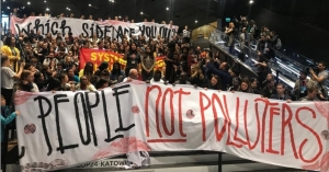 """Large crowd holding sign that says """"people, not polluters."""""""